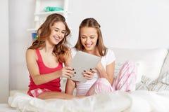 Lyckliga vänner eller tonåriga flickor med minnestavlaPC hemma royaltyfria foton