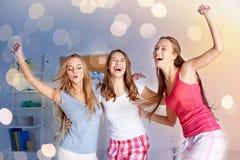 Lyckliga vänner eller tonåriga flickor som har gyckel hemma arkivbild