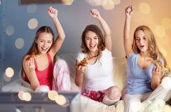 Lyckliga vänner eller tonåriga flickor som hemma äter pizza arkivfoto