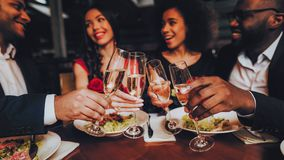 Lyckliga vänner för grupp som tycker om att datera i restaurang arkivfoto