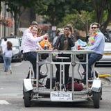 Lyckliga vänner firar bröllopet, trampar pedalbusen, drinköl Royaltyfri Fotografi