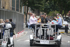 Lyckliga vänner firar bröllopet, trampar pedalbusen, drinköl Royaltyfri Foto