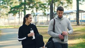 Lyckliga vänner flicka och bärande träningsoveraller för grabb talar och dricksvatten från flaskor, efter utomhus- övning har par stock video