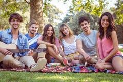 lyckliga vänner i en parkera som har en picknick royaltyfria bilder