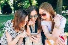 Lyckliga vänner i parkera på en solig dag Sommarlivsstilståenden av tre blandras- kvinnor tycker om den trevliga dagen som bär arkivbild