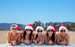 Lyckliga vänner i santa hattar på stranden på jul royaltyfri bild