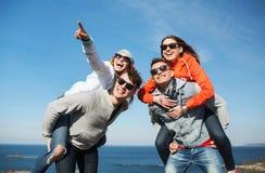 Lyckliga vänner i skuggor som har roligt utomhus Royaltyfri Foto