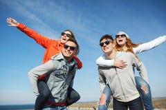 Lyckliga vänner i skuggor som har roligt utomhus Fotografering för Bildbyråer