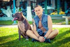 Lyckliga vänner man och gropbull terrier för hunden amerikanskt sammanträde på gräs parkerar in Arkivfoto