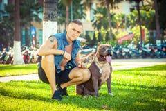 Lyckliga vänner man och gropbull terrier för hunden amerikanskt sammanträde på gräs parkerar in Arkivbild