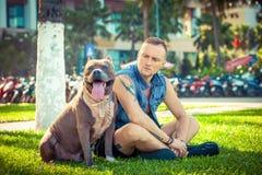 Lyckliga vänner man och gropbull terrier för hunden amerikanskt sammanträde på gräs parkerar in Royaltyfri Fotografi