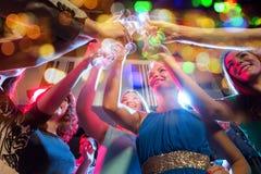 Lyckliga vänner med exponeringsglas av champagne i klubba Arkivbild
