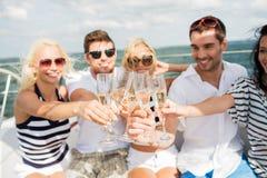 Lyckliga vänner med exponeringsglas av champagne på yachten Arkivbilder