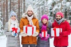 Lyckliga vänner med gåvaaskar i vinterskog Arkivfoton
