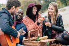 Lyckliga vänner med gitarren på den alfresco picknicken fotografering för bildbyråer