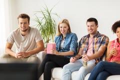 Lyckliga vänner med hållande ögonen på tv för popcorn hemma Royaltyfria Bilder