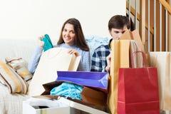 Lyckliga vänner med kläder och shoppingpåsar Arkivbilder