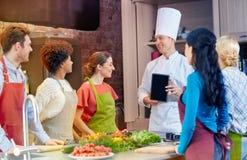 Lyckliga vänner med kock- och minnestavlaPC i kök royaltyfria foton