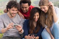 Lyckliga vänner med mobiltelefonen Royaltyfri Fotografi