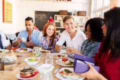 Lyckliga vänner med pengar som betalar på restaurangen Arkivbilder