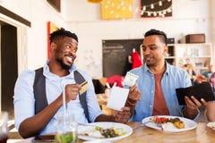 Lyckliga vänner med pengar som betalar räkningen på restaurangen Royaltyfri Fotografi