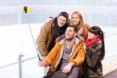 Lyckliga vänner med smartphonen på att åka skridskor isbanan Arkivfoton