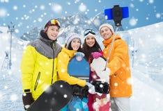 Lyckliga vänner med snowboards och smartphonen Arkivbild