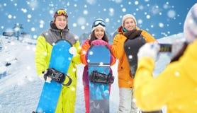 Lyckliga vänner med snowboards och smartphonen Arkivfoto