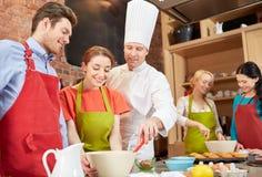 Lyckliga vänner och kocken lagar mat bakning i kök Arkivfoton