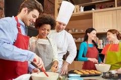 Lyckliga vänner och kocken lagar mat bakning i kök Arkivbild