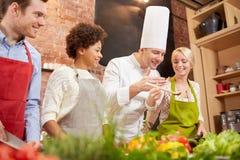 Lyckliga vänner och kocken lagar mat matlagning i kök Royaltyfri Bild