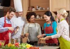 Lyckliga vänner och kocken lagar mat matlagning i kök Arkivbilder