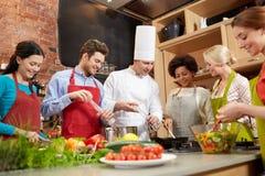 Lyckliga vänner och kocken lagar mat matlagning i kök Arkivfoto