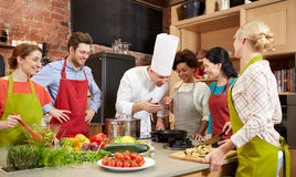 Lyckliga vänner och kocken lagar mat matlagning i kök royaltyfri fotografi