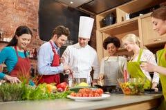 Lyckliga vänner och kocken lagar mat matlagning i kök fotografering för bildbyråer