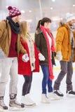 Lyckliga vänner på att åka skridskor isbanan Arkivfoton