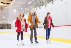 Lyckliga vänner på att åka skridskor isbanan Arkivfoto