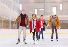 Lyckliga vänner på att åka skridskor isbanan Royaltyfri Bild