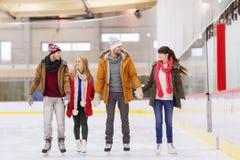 Lyckliga vänner på att åka skridskor isbanan Arkivbild