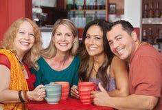 Lyckliga vänner på cafen bordlägger Royaltyfri Foto