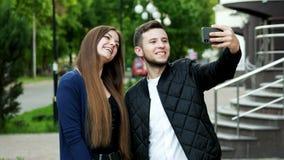 Lyckliga vänner på gatan som har video pratstund med med föräldrar via den smarta telefonen arkivfilmer