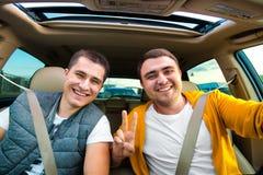 Lyckliga vänner som är klara för semestrar som kör bilen Royaltyfri Foto