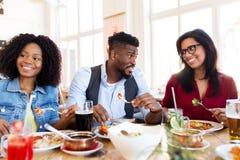 Lyckliga vänner som äter och talar på restaurangen royaltyfri foto