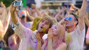 Lyckliga vänner som dansar och att filma videoen på smartphonen, holifestival, ultrarapid lager videofilmer