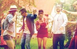 Lyckliga vänner som dansar på sommar, festar i trädgård arkivfoto