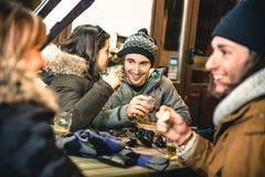 Lyckliga vänner som dricker öl och äter chiper vid natt arkivbilder