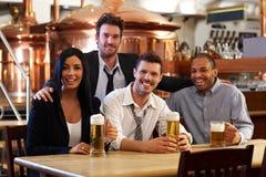 Lyckliga vänner som dricker öl på puben Arkivbild