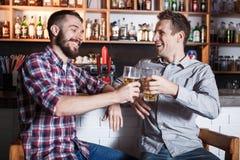 Lyckliga vänner som dricker öl på räknaren i bar arkivbilder