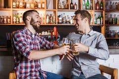 Lyckliga vänner som dricker öl på räknaren i bar arkivbild