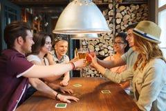 Lyckliga vänner som dricker öl på stången eller baren Royaltyfri Fotografi